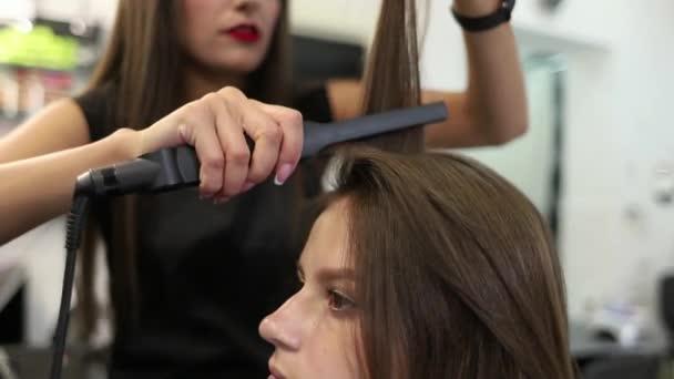 Close-up shot ženy s vlasy narovnala v kadeřnictví. Kulma zastřelil v pomalém pohybu. HD