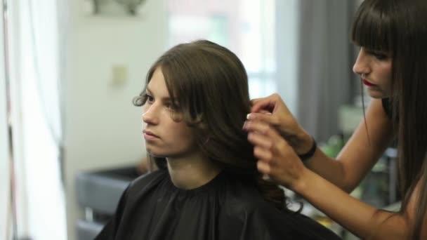 A fodrász teszi a frizura a nő. Fodrász közelről. Olló és a fésű, a stylist. Egy fiatal hölgy gyönyörű haj
