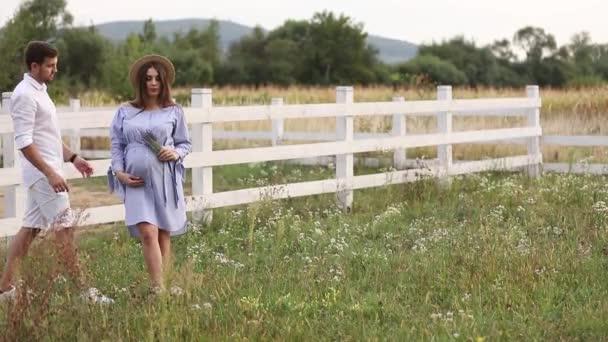 Er und seine schwangere Frau stehen auf einem Feld in der Nähe des Hofes und umarmen sich. Mann geht zu seiner Frau -Video