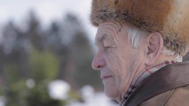 Primo piano di un uomo anziano in cappello di inverno. Uomini vecchi hanno misthins sul viso. Nonno felice