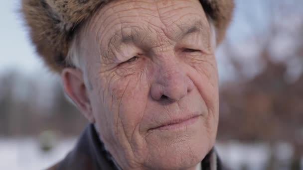 Closeup starší muž v zimní čepice. Starý muž si misthins na tvář. Happy dědeček