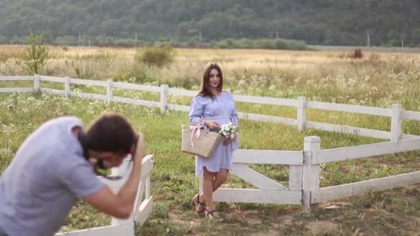 Fotograf fotografování krásná těhotná žena oblečená v modrých šatech a pletené čepice. Položila ruce na jejím břiše. Focení v poli poblíž farmy. Letní čas