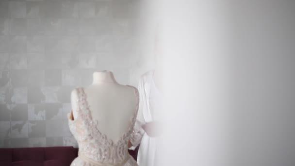 Sexy Braut Brautkleid stehen. Schöne Mädchen Blick auf das Kleid. Braut zu Hause. Morgen