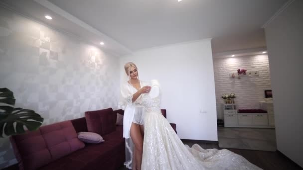 Sexy bride standing by her wedding dress. Beautiful girl look at the dress. Bride at home. Morning