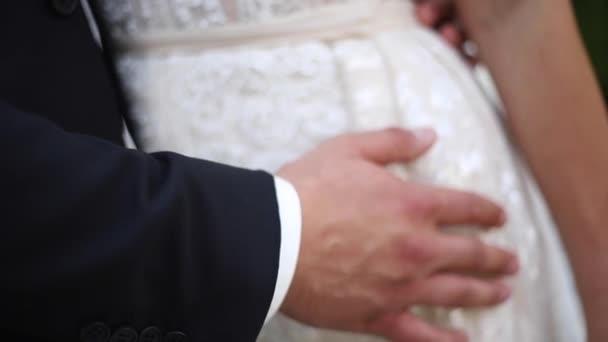 Nahaufnahme der hand Braut und Bräutigam. Elemente der Hochzeit. Anzug und Kleid
