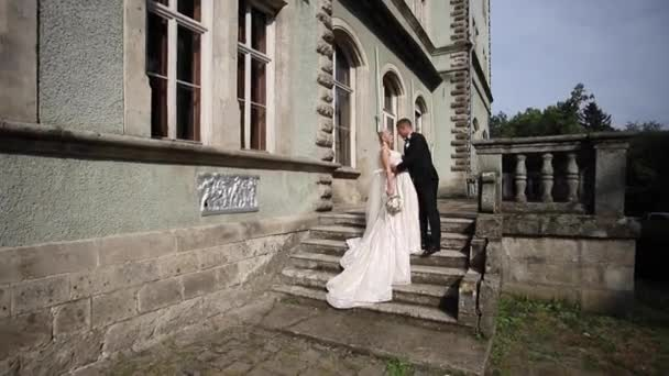 Groom and bride stand on stairs. Fashion model in elegant clothes. White long dress and stylish suit