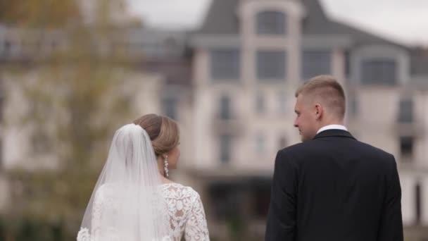 Šťastné novomanželé, co chodí v parku. Elegantní nevěsta a ženich venku