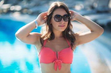 Sexy woman in bikini enjoying summer sun and tanning during holidays in pool