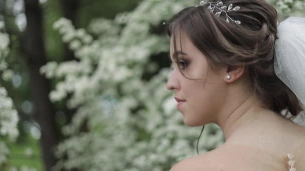 Bájos menyasszony gyönyörű menyasszonyi ruha tartsa csokor és állj előtt virágzó fák