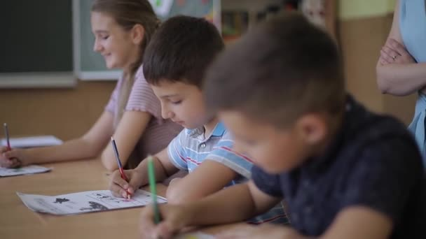 Teacher helping school kids writing test in classroom. education, elementary school, learning and people concept
