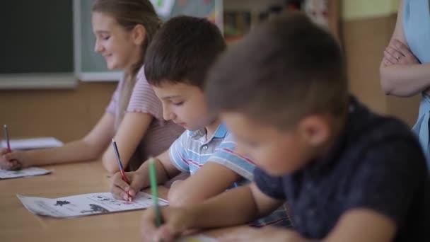 Učitel pomáhá dětem ve škole psát testy ve třídě. školství, základní škola, výuka a koncepce lidí