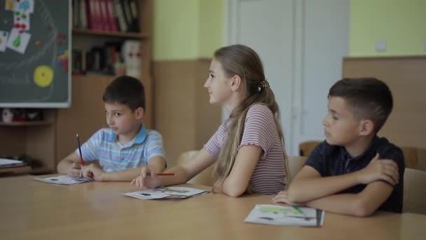 Bildung, Grundschule. Lern- und Personenkonzept - Schülergruppe mit Stiften und Notizbüchern Schreibtest im Klassenzimmer