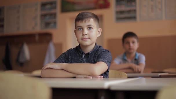 Happy little children in elementary school. Boys and girls study. Children raise hand up