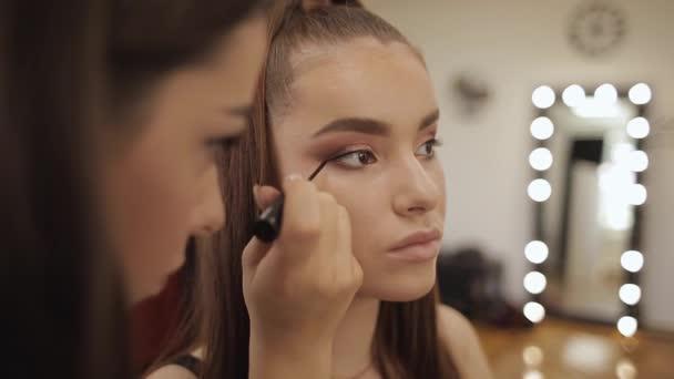 Model má make-up podle malíře v kadeřnictví krásy. Zobrazení první osoby. Redhead model s pihami. Uzavření modelů s obličejem vzhůru