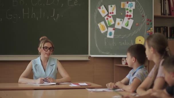 Tanárnő a gyerekek előtt. Szép tanár osztályban ül az íróasztalon, és kérte a gyermekeket. oktatás, általános iskola, tanulás és az emberek fogalma-