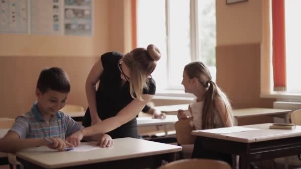 Lehrer helfen Schülern beim Schreiben von Tests im Klassenzimmer. Bildung, Grundschule, Lernen und Menschen-Konzept