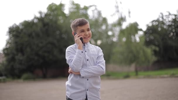 Handsome boy use phone outside. Little boy on the back yard of school