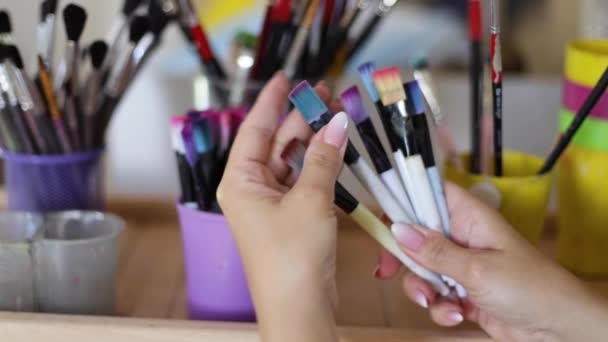 Woman choose brush for painting. Art concept. A lot of brushes in Drawing studio. Close up of hands with brush