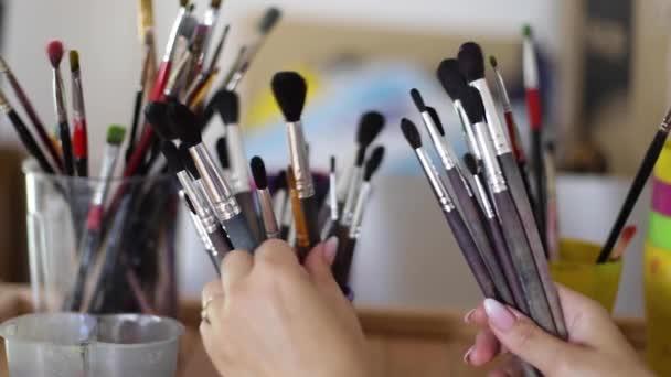 Žena vybere štětec pro malování. Koncepce umění. Hodně stop štětců v kreslicím studiu. Zavření rukou štětcem
