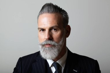 Portrait of elegant middle aged bearded gentleman wearing trendy suit over empty gray background. Studio shot, business fashion concept.