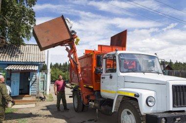 İşçiler özel bir araba çöp kamyonuna atık yüklüyorlar. Uzman bir araba çöpü temizler.