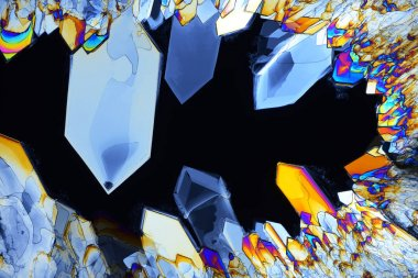 Colorful micro crystals in polarized light. Photo through a micr