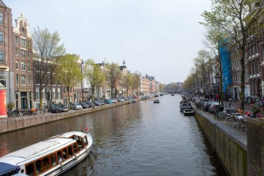 Amsterdam/Netherlands, April 06, 2019: Old streets along numerous canals in Amsterdam. River transport and bicycles