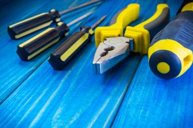 Hand tool on blue wooden background for home work or for locksmith.