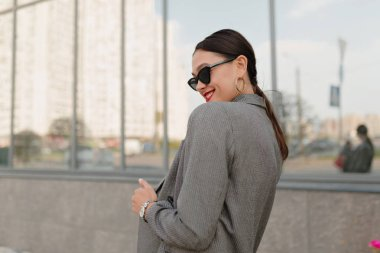 Portrait of back of exited charming lady with dark hair, wearing stylish jacket and sunglass turn around and smilinf