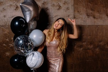 Excited funny girl in elegant casual outfit with balloons dancing and showing peace sign over isolated dark background