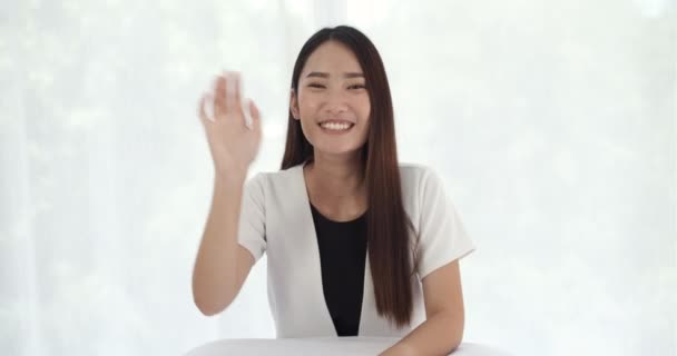 Young asian woman looking at cam talking laughing at home, happy female blogger speaking to webcam make video conference call online dating chat or recording blog vlog sit on sofa.