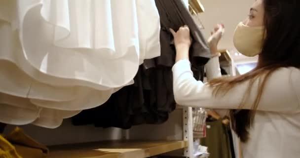 Junge asiatische Frau mit Gesichtsmaske und neuem normalen Lebensstil wählt T-Shirt-Kleidung in Kaufhaus, Einkaufszentrum nach der Coronavirus-Pandemie beendet Lockdown und Wiedereröffnung Geschäft.