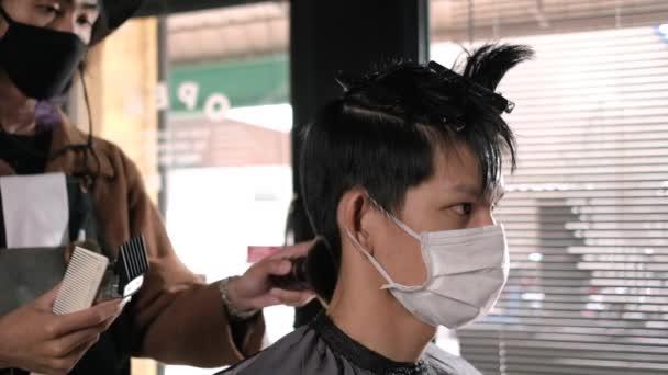 Seitenansicht Zeitlupe: Friseursalon Friseursalon Schlangestehen Kunden tragen Mundschutz Prävention Geschäft nach Coronavirus Lockdown wieder geöffnet, Männer Frisur und neuer normaler Lebensstil.