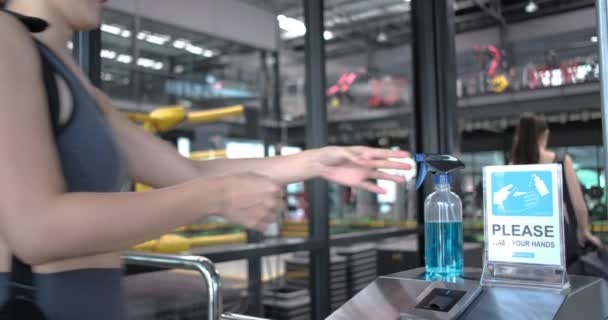 Wiedereröffnung des Fitnessstudios, Frau in Sportbekleidung wäscht sich die Hände mit Desinfektionsmittel, während sie sich in der Lobby eines Fitnessstudios aufhält. Vor dem Training in einem Fitnessstudio während der Coronavirus-Epidemie, Gesunder Lebensstil.