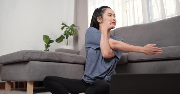 Sportos fiatal ázsiai nő csinál nyújtás és néz fitness videó bemutató online laptop súlyzókkal a nappaliban, Sport otthon edzés, online fitness osztály, egészséges életmód.