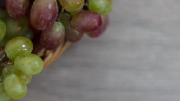 Fresh ripe grapes in wicker basket on kitchen table