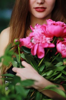 Bouquet of Peony. Stylish fashion photo of beautiful young woman lies among peonies. Holidays and Events. Valentines Day. Spring blossom. Summer season
