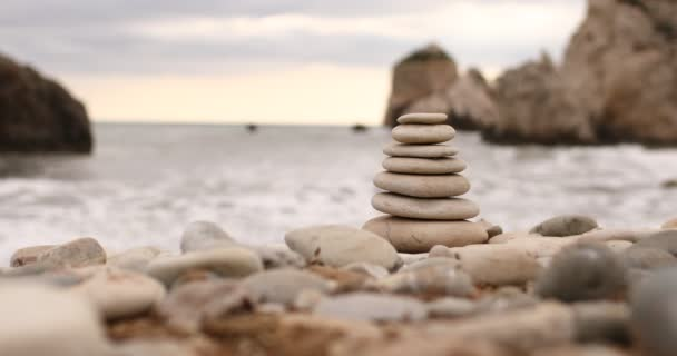4k video of Pyramid stones on the seashore on a sunny day on the blue sea background. Happy holidays. Pebble beach, calm sea, travel destination. Concept of happy vacation on the sea.