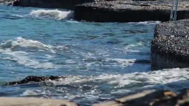A meleg tenger hullámai verte a parton egy csendes napsütéses napon, fröccsenő víz. közeli kép:.