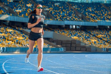 Female athlete sprinting on a running track in a stadium.