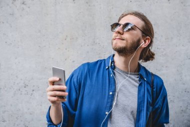 Portrait of a smiling young man in casual clothes listening to music with earphones and mobile phone isolated over grey background