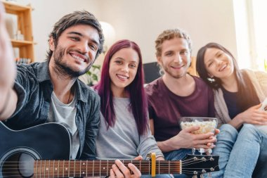 Smiling friends in casual on couch at home with guitar making selfie