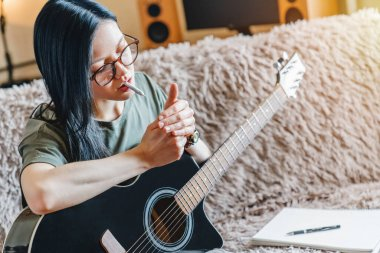 Young girl lighting marijuana joint while holding guitar at home
