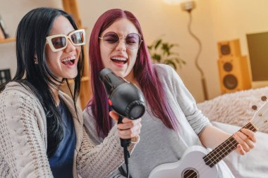 Young funny girls dancing and singing with hairdryer and ukulele at home