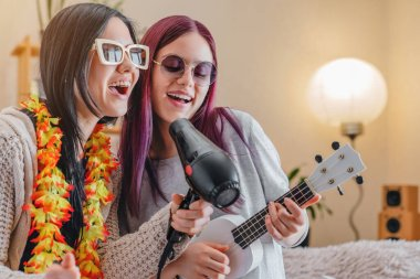 Young joyful girls in sunglasses dancing and singing with hairdryer and ukulele at home
