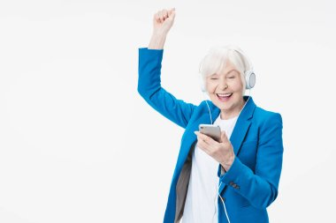 Elderly cheerful woman with headphones listening music on phone and dancing isolated on white background