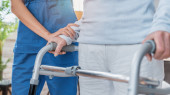 Photo Cropped image of nurse helping senior woman to walk with walker at home
