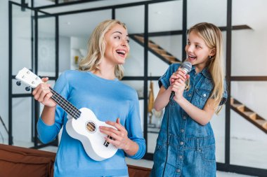 Mom and cute little girl with microphone singing together and playing ukulele