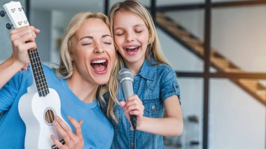 Caucasian mother with little girl singing in karaoke at home