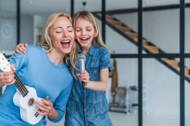Beautiful mother and her cute little daughter with microphone singing together and playing ukulele